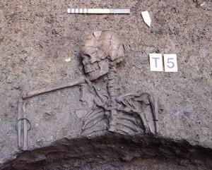 Una tomba parzialmente distrutta; al braccio del defunto è visibile un bracciale in bronzo, © Soprintendenza per i Beni Archeologici del Piemonte e del Museo Antichità Egizie.