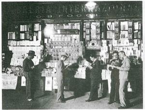 Chiosco della Libreria Internazionale G.B. Fogola nei portici di piazza Carlo Felice, di fronte all'Hotel Ligure, chiuso nel 2010, ripresa 1924-1925 (riproduzione da libro: A. Job, M. L. Laureati, C. Ronchetta, 1984, p. 156, n. 296)