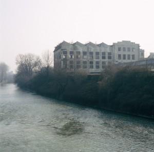 La palazzina del reparto cottura pneumatici vista dalla sponda sinistra del fiume Dora. Fotografia di Filippo Gallino per la Città di Torino, febbraio 1998.