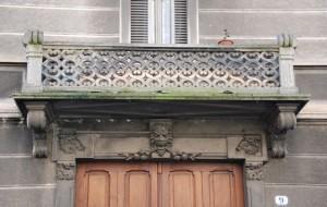 Particolare dei balconi in litocemento e degli elementi decorativi del portale di ingresso, via Belmonte 9. Fotografia di Giuseppe Beraudo, 2011