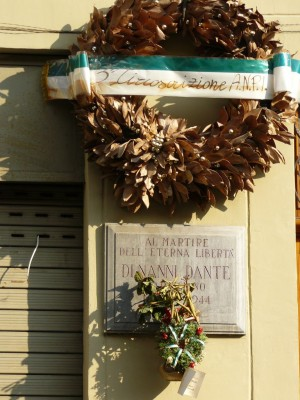 Particolare della lapide e della corona posta dall'Anpi davanti al portone della casa in cui morì Di Nanni.© Museo Diffuso della Resistenza, della Deportazione, della Guerra, dei Diritti e della Libertà.