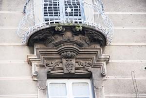 Particolare dei balconi dell'ultimo piano e degli elementi decorativi in litocemento dei sovra porte. Fotografia di Giuseppe Beraudo, 2011
