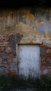 Particolare di una pittura parietale e della porta sottostante presenti alla cascina Verna di via Corniliano d'Alba 3. Fotografia di Edoardo Vigo, 2012.