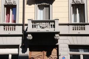 Particolare delle decorazioni a fronde in litocemento dei balconi e dei sovra finestre, casa in via Lauro Rossi 26. Fotografia di Giuseppe Beraudo, 2011