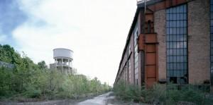 Il fronte dei capannoni dei laminatoi; sulla sinistra il serbatoio idrico ancora esistente. Fotografia Filippo Gallino per la Città di Torino, aprile 2000.